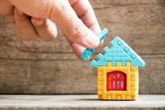 Man hold piece of puzzle to complete the home model. Object on wood background Concept of dream home, mortgage investment, family fulfillment Stock Photo