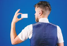 Man hold plastic blank card blue background rear view. Take this card. Banking and credit concept. Plastic bank card. Easy money credit. Which bank credit card stock images