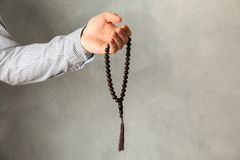 Man hold prayer beads in hand. Against grey background stock photography