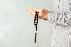 Man hold prayer beads in hands. Against grey background royalty free stock images