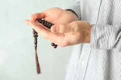 Man hold prayer beads in hands. Against grey background royalty free stock image