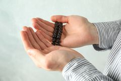 Man hold prayer beads in hands. Against grey background royalty free stock photos