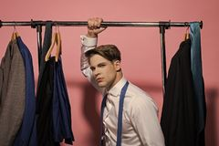Man hold rack with jackets on hangers in wardrobe. Businessman in white shirt, blue necktie on pink background. Business fashion, style concept. Clothing stock photos