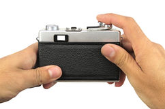 Man hold retro camera from back in hand on white background Royalty Free Stock Images