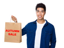 Man hold a shopping bag for showing phrase of autumn sale Stock Photography