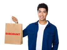 Man hold a shopping bag for showing a word discount. Isolated on white background Stock Images