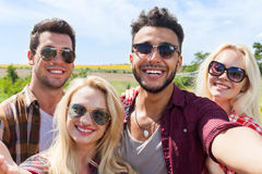 Man hold smart phone camera taking selfie photo friends face smile close up. Countryside young people group outdoor two couple summer sunny day Stock Images