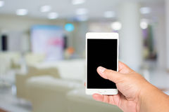 Man hold smart phone on lobby to see doctor background. Stock Images