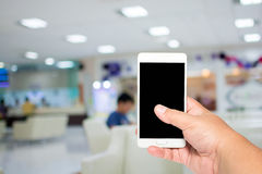 Man hold smart phone on lobby to see doctor background. Royalty Free Stock Images