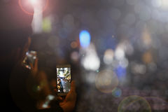 Man hold smart Phone and take photo vdo of pop star fashion show. On stage catwalk with a lot of people, many lights blur bokeh flare royalty free stock image