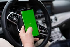 Man hold smartphone in car on dashboard background royalty free stock photo