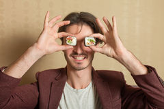 Man hold sushi rolls instead of eyes Stock Photo
