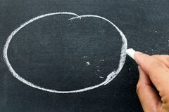 Man hold white chalk to write something on black board. With circle background Concept for business or education by have space to add text Royalty Free Stock Photography
