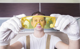 Man hold yellow safety glasses. Worker in work uiform Royalty Free Stock Photo