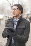 Man holdin ipad tablet computer on street Royalty Free Stock Photography