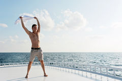 Man Holding A Shirt Over His Head Against Sea Sunset Royalty Free Stock Photos