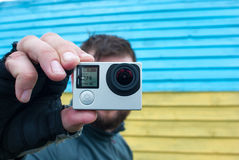 Man holding action camera.  The colors of Ukrainian flag Stock Photos