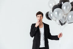 Man holding air balloons and smoking cigarette Royalty Free Stock Photography