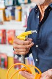 Man Holding Air Compressor Hose In Shop. Cropped image senior man holding air compressor hose in hardware shop Stock Image