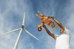 Man Holding Airplane Kite At Wind Farm Stock Photography