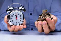 Man Holding Alarm Clock And Golden Coins stock photo