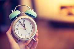 Man is holding an alarm clock in the hand, blurry background. Man is holding an alarm clock, sunshine in the morning, blurry background time history stand up nap royalty free stock image