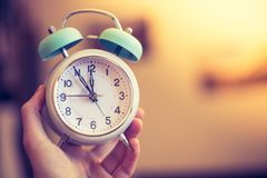 Man is holding an alarm clock in the hand, blurry background. Man is holding an alarm clock, sunshine in the morning, blurry background time history stand up nap stock photos