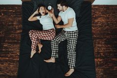 Man is Holding Alarm Clock near Woman`s Ear on Bed stock photography