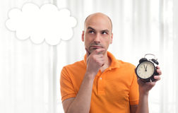 Man holding alarm clock, thinking and looking up Stock Images