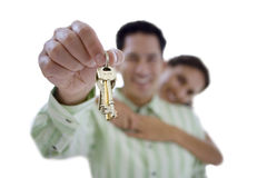 Man holding aloft keys, smiling, portrait, cut out Royalty Free Stock Photo