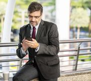 Man Holding Android Smartphone Sitting on Brown Marble Pavement stock photo