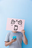 Man holding angry expression billboard. And take phone isolated on blue background Stock Image