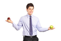 Man holding an apple and a cake Royalty Free Stock Images
