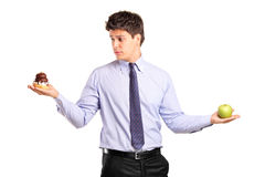Man holding an apple and slice of cake Stock Photography