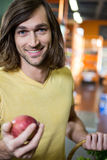 Man holding apple in supermarket Royalty Free Stock Image