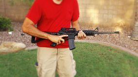 Man with AR-15 Quickly Loads a New Magazine. 7185 A man holding an AR-15 rifle shows how quickly the gun may be reloaded stock video