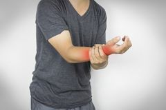 Man holding arm ache, concept as health care. On gray background stock photo