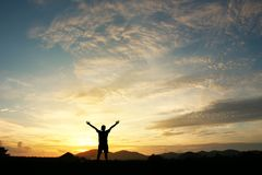 Man holding arms up. In praise to God against sunrise at morning background royalty free stock photo