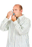 Man holding asthma medicine inhaler. With both hands stock photo