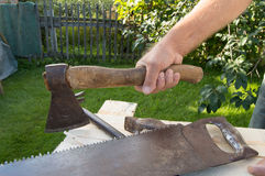 Man holding the axe, working with construction tools in his garden.  Royalty Free Stock Images