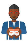Man holding baby booties. An african-american man holding baby booties in hands vector flat design illustration isolated on white background stock illustration