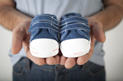 Man holding baby shoes Stock Photos