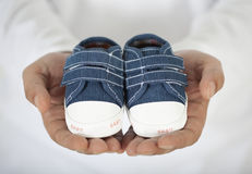 Man holding baby shoes in white Stock Photos