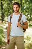 Man holding backpack and standing in forest. Handsome young man holding backpack and standing in forest Stock Photo