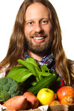 Man holding a bag of fresh fruit and vegetables. Goodlooking and healthy man dressed like a hippie holding a bag of fresh, organic fruit and vegetables. Isolated stock images