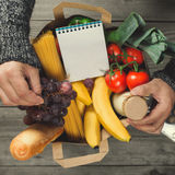 Man holding bag full of food with blank notepad Royalty Free Stock Images