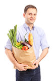Man holding a bag full of groceries. Isolated on white background Royalty Free Stock Photo