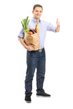 Man holding a bag of groceries and giving thumb up Royalty Free Stock Photos