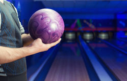 Man with bowling ball. Man holding ball against bowling alley Stock Images