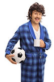 Man holding a ball and a coffee cup. Vertical shot of a young man in a bathrobe holding a football and a coffee cup isolated on white background Stock Photography